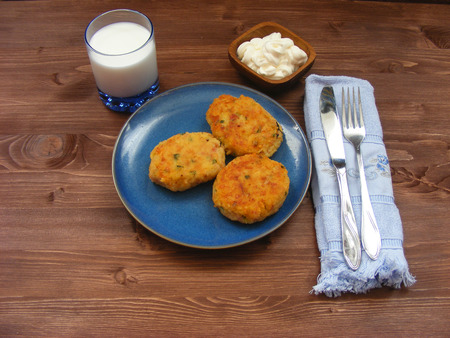 Rissoles of ham, cheese  and potatoes on blue plate, milk in glass and sour cream in wooden bowl on rustic background with blue napkin and cover Zdjęcie Seryjne