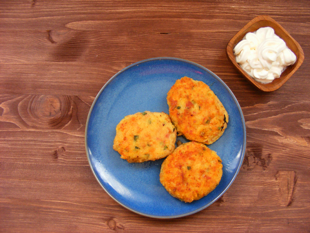 Rissoles of ham, cheese  and potatoes on blue plate and sour cream in wooden bowl on rustic background flat view