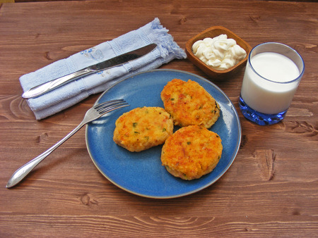 Rissoles of ham, cheese  and potatoes on blue plate, milk in glass and sour cream in wooden bowl with blue napkin and cover Zdjęcie Seryjne