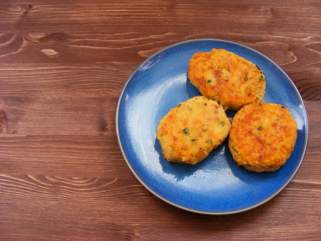 Rissoles of ham, cheese  and potatoes on blue plate on rustic wooden background Zdjęcie Seryjne