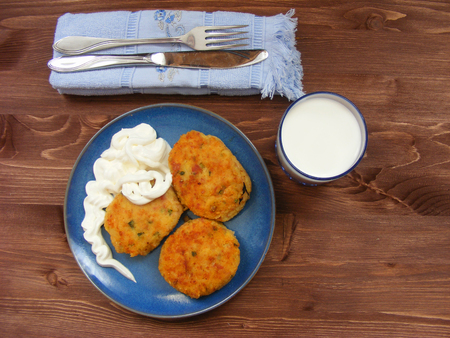 Rissoles of ham, cheese  and potatoes on blue plate, milk in glass and sour cream in wooden bowl on rustic background with cover on blue napkin flat view