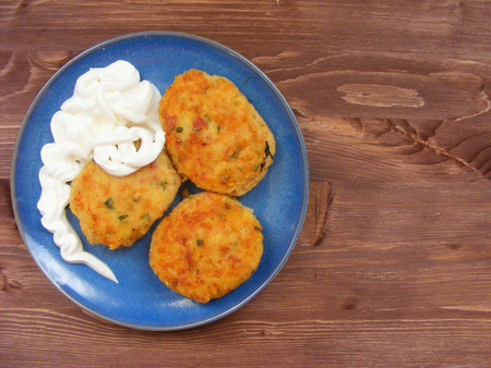 Rissoles of ham, cheese  and potatoes with sour cream on blue plate on rustic wooden background Zdjęcie Seryjne
