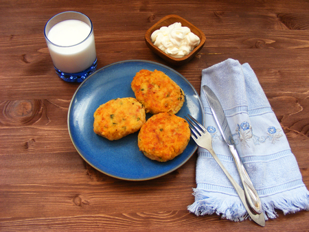 Rissoles of ham, cheese  and potatoes on blue plate, milk in glass and sour cream in wooden bowl on rustic background with blue napkin
