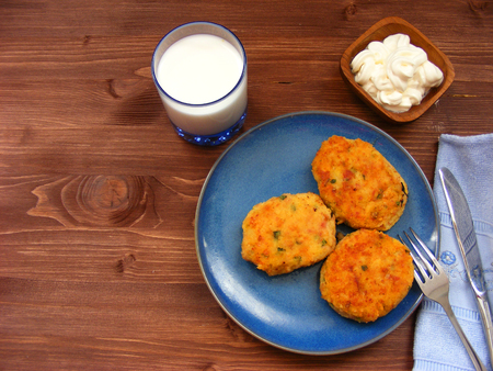 Rissoles of ham, cheese  and potatoes on blue plate, milk in glass and sour cream in wooden bowl on rustic background