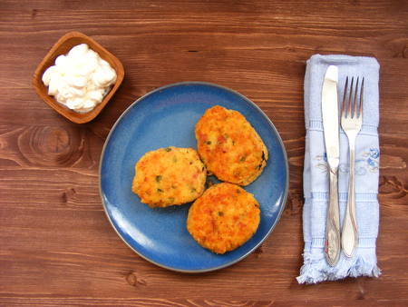 Rissoles of ham, cheese  and potatoes on blue plate and sour cream in wooden bowl on rustic background with blue napkin and cover Zdjęcie Seryjne