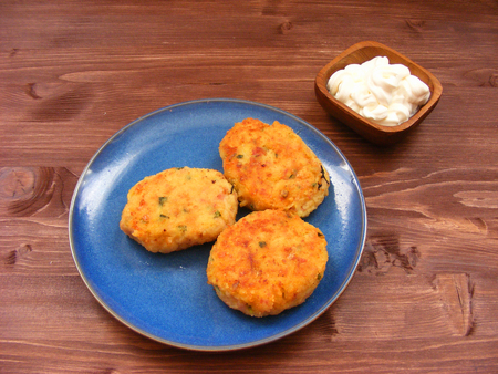 Rissoles of ham, cheese  and potatoes on blue plate and sour cream in wooden bowl on rustic background