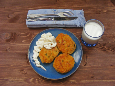 Rissoles of ham, cheese  and potatoes on blue plate, milk in glass and sour cream in wooden bowl on rustic background with cover on blue napkin