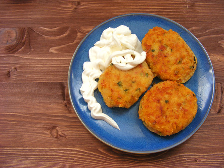 Rissoles of ham, cheese  and potatoes with sour cream on blue plate on  wooden background