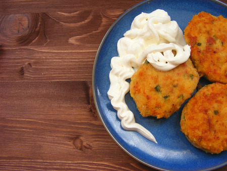 Rissoles of ham, cheese  and potatoes with sour cream on blue plate on rustic wooden background flat view Zdjęcie Seryjne