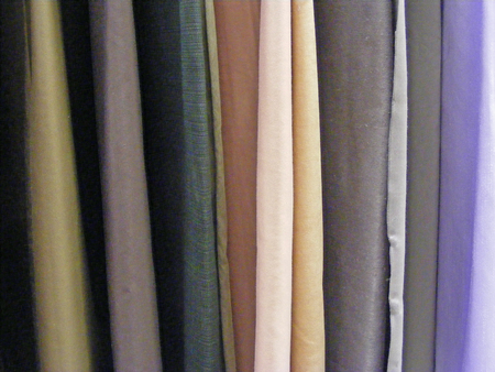 Selection of colorful fabrics for curtains, rolls of fabrics. Woolen, textiles. Фото со стока