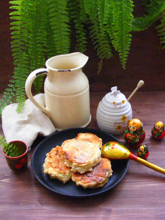 Russian cuisine : crepes pancakes on black cast iron with oak flakes on  wooden table with rustic milk jug and nesting dolls matrioshka