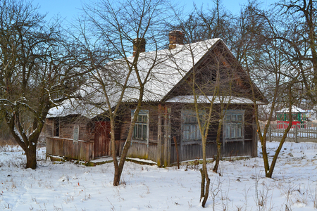 Abandoned old russian wooden house. Timber texture. Home exterior. Winter landscape.