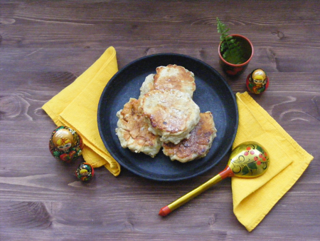 Traditional russian cuisine : pancakes  with oak flakes on cast iron and nesting dolls matreshka and traditional spoon, yellow napkin on wooden background Stockfoto