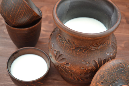 Close up: organic goat milk in pottery in russian style on rustic wooden table
