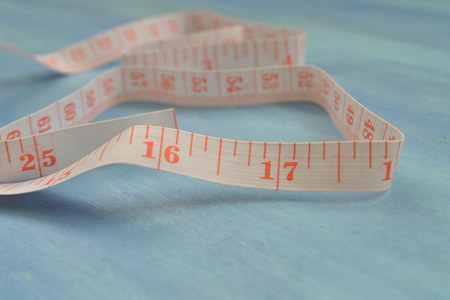 Tape measure half-rolled out. Measuring cm and inches. Tailoring tools. Pocket measure. Imagens