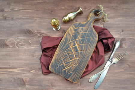 Wooden rustic background. Dark brown cutting board with silver knife and fork. Organic nutrition.