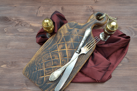 Red wood cutting board with silver pepperbox and fork on dark background. Brown shabby wooden table. Concept of healthy diet. Imagens
