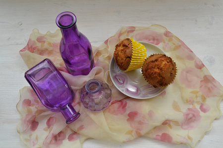 Chocolate cupcakes on a dessert table with vintage shawl and purple bottles