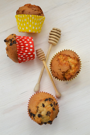 Assortment of brightly decorated honey cupcakes, vertical image