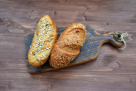 Freshly baked bread from wheat flour with sunflower seeds, pumpkin, sesame flat lay on aged wooden cooting board