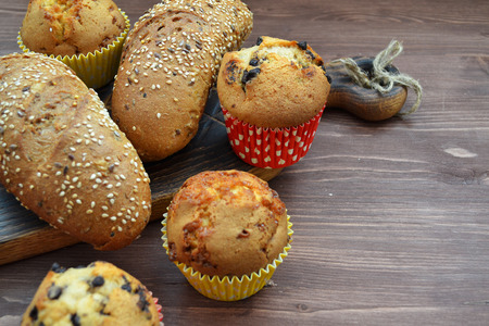 Fresh bread with seeds and mix cupcakes lies on a old wooden background. Imagens