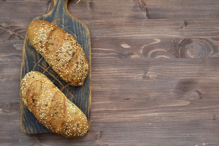 Two freshly baked crunchy bread rolls with a golden crust on wooden cutting board and copy space on wooden background