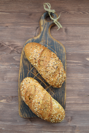 Bun with sesame seeds on old wooden cutting board, vertical photo