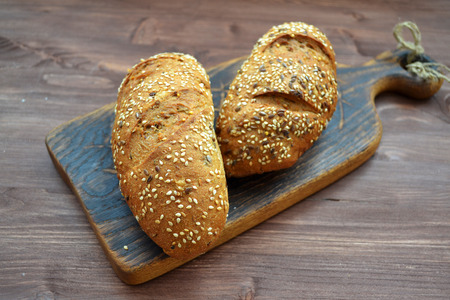Bread sprinkled with sesame seeds on a wooden table. The concept of healthy organic food.