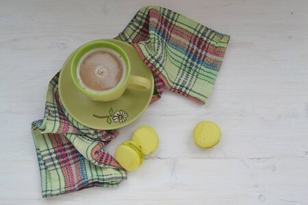 Top view image of green cup of coffee and pistachios macaron or macaroon over white wooden background