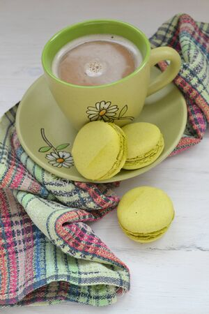 Pistachio macaron macaroon cookie dessert from France, vertical photo with coffee cup