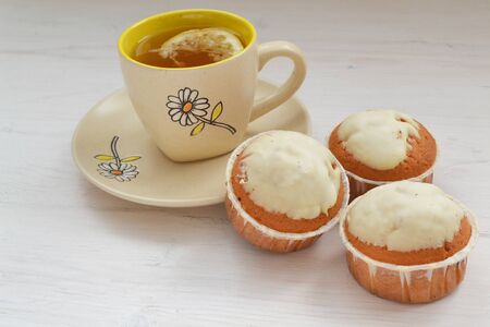 Lemon cupcakes with white icing and cup of tea