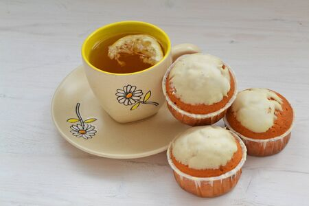 Sweet cupcakes on shabby wooden table with cup of tea