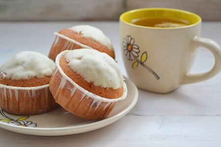 Closeup of lemon cupcakes with  cup of tea