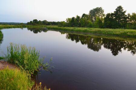 River landscape on a summer evening in Belarus, river Schara at Slonim village. Summer nature river landscape. Picturesque nature, rural river landscape