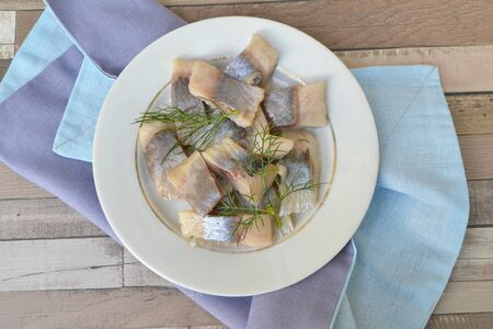 Salted herring slices with spice, herbs and dill on rustic plate and blue napkin Banque d'images - 128235887