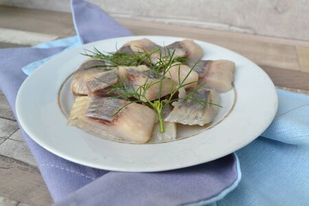 The Salted fish herring with dill on rustic white plate