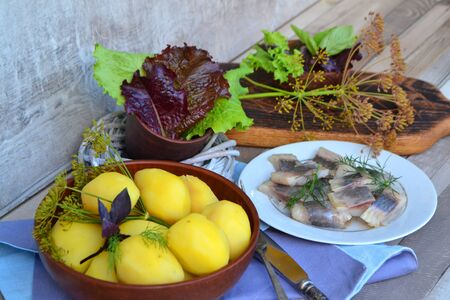 Salted herring with onions and dill served with boiled potatoes. Rustic style