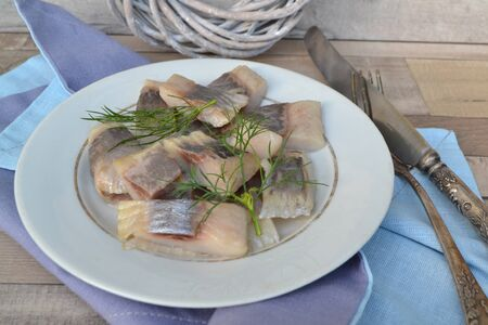 Matjes Herring with herbs on old plate and rustic shabby table Reklamní fotografie