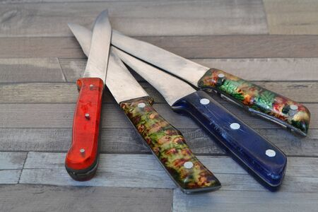 Red, violet hand made knifes in retro style on shabby table