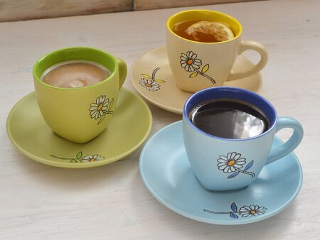 Colorful cups with hot coffee, cappuccino and tea. Set with different cups of coffee and tea