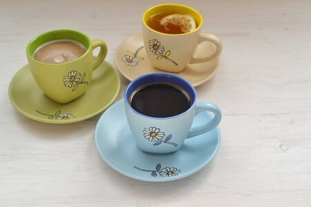 Coffee, cappuccino and Tea in colorful cups  on shabby table