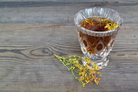 Cup of herbal tea from Hypericum: tincture or decoction of St Jonh`s wort grass in crystal glass on black table. St. John`s wort medicinal. Homeopathy. Liquid, dried.