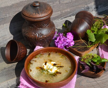 Cabbage soup and sour cream on pink napkin on the table. Russian traditional dish Ceramic brown rustic jug