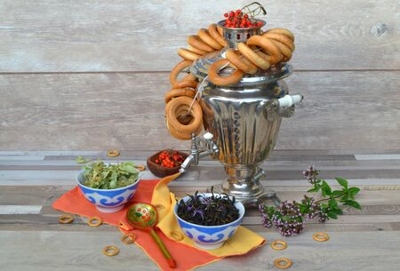 Russian cuisine: samovar on a wooden background with bagels and tea (linden, mint and blooming sally)