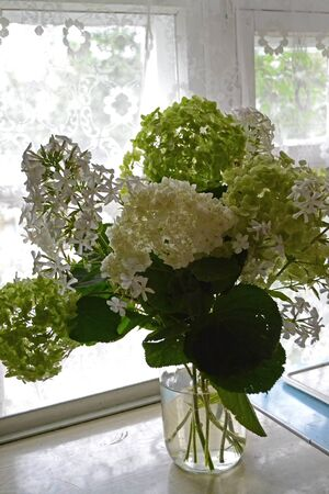 Large lush bouquet of white hydrangea and phlox. Vertical image, country style