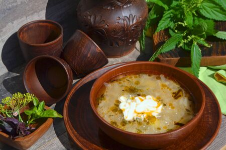 Russian cuisine: country soup with nettle on rustic table on ceramic bowl
