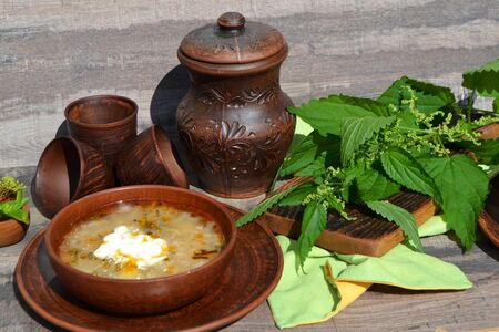Nettle soup in a ceramic rustic bowl on a wooden surface, with ceramic jug Stock fotó