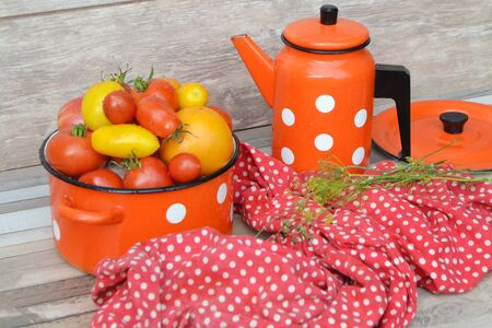 Yellow and red cherry tomatoes in the casserole, red casserole and teapote with white dots pattern, russian style