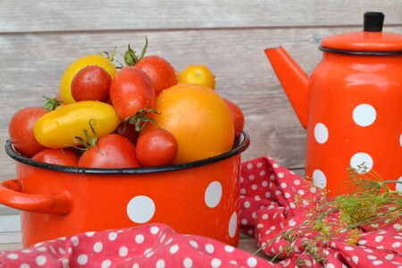Cherry tomatoes close up in a casserole on rustic background, russian style