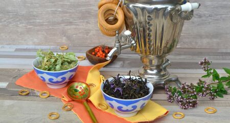 Traditional russian samovar on shabby table, a symbol of hospitality. Crispy bagels, drying or bagels and herbal linden and mint tea